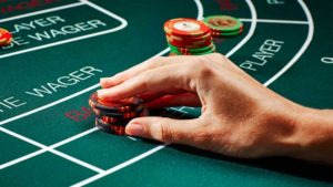 a hand playing baccarat casino game